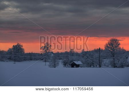 Bright Pink Sunset Over Snowcovered Winter Countryside With A Cottage