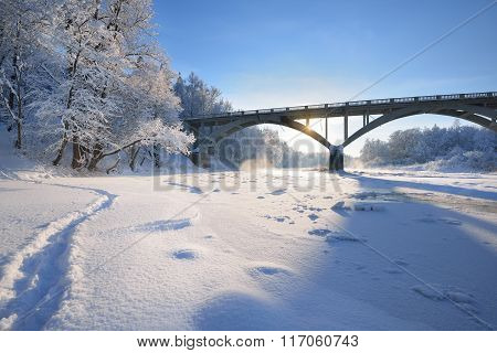 View Of A Bridge Over A Frozen River Surrounded By Snowcovered Deciduous Trees