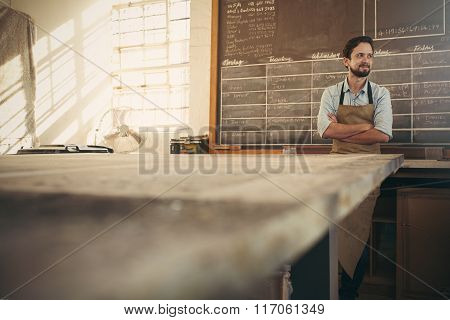 Craftsman in his workshop looking away with arms crossed confide