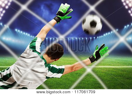 Back view of the goalkeeper catching the ball on the football field