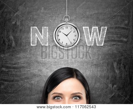 A young woman looking in front of her and tthinking about present opportunities and time. A pocket watch and the word 'now' over her head. Black background. Front view. Concept of present moment. poster
