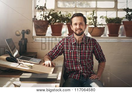 Confident entrepreneur designer sitting in his office space