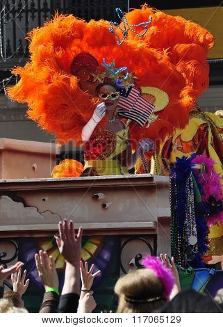 NEW ORLEANS - FEBRUARY 17, 2015: A lady masker in orange and red on parade float throws beads