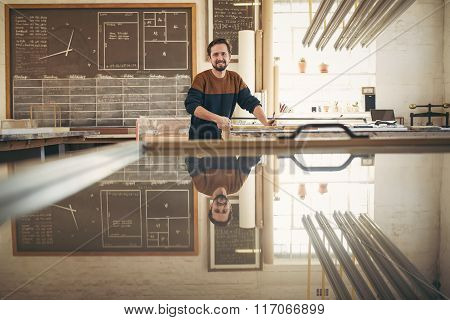 Smiling professional framer in his studio working