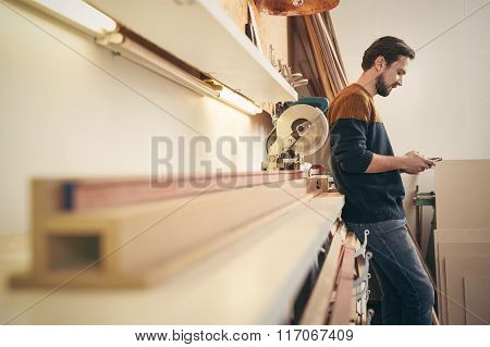 Craftsman using cell phone in his workshop