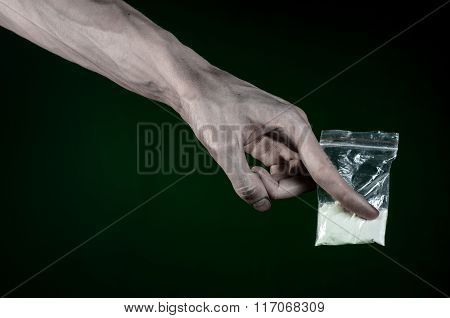 The fight against drugs and drug addiction topic: dirty hand holding a bag addict cocaine on a dark green background poster
