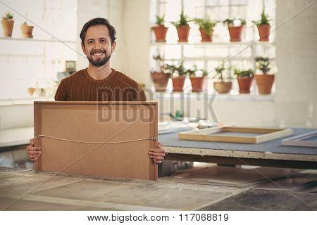 Professional framer in his studio workshop smiling