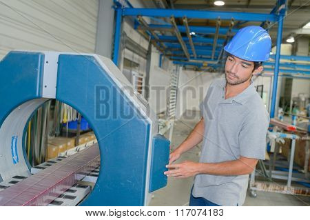 Factory worker controlling machine