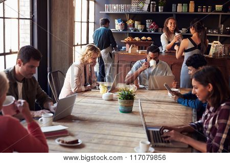 Interior Of Coffee Shop With Customers Using Digital Devices