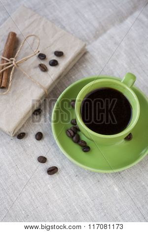 Green Cup Of Coffee With Coffee Beans And Vintage Notebook