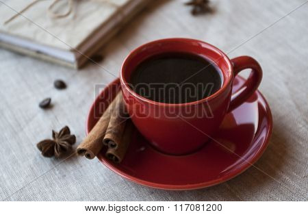 Red Cup Of Coffee With Coffee Beans And Spices Cinnamon And Anise Star
