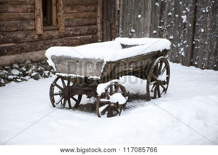 Old wooden cart in the courtyard peasant Estonian villages in winter in the snow