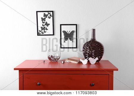 Room interior with red wooden commode, vase and frames on light wall background