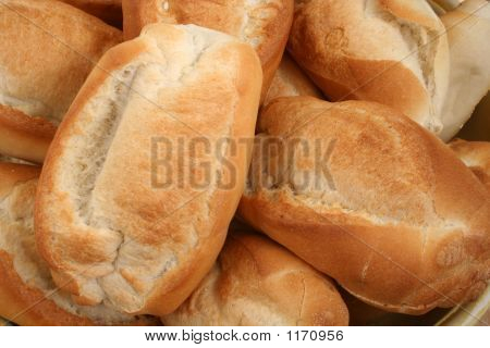 a number of fresh bread rolls are displayed. poster