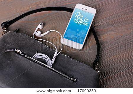 Ladies handbag and smartphone with romantic screensaver on gray background
