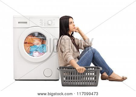 Young bored woman sitting by a washing machine and waiting for the laundry isolated on white background