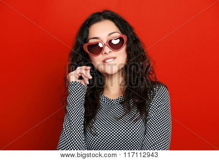 beautiful girl glamour portrait on red in heart shape sunglasses, long curly hair