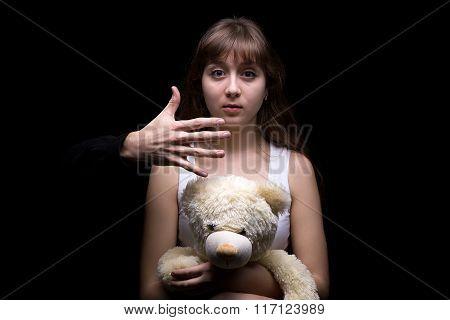 Scared teenage girl with teddy bear