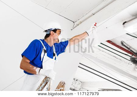 Worker Spraying Ceiling With Spray Bottle