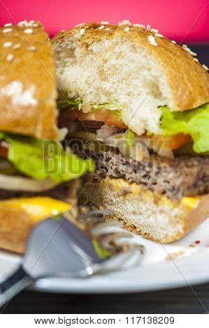Appetizing hamburger with vegetables on white plate with fork on wooden table.