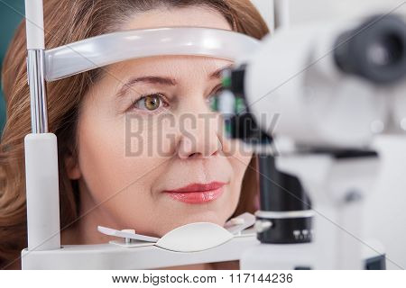 Cheerful lady having eye examination in oculist office