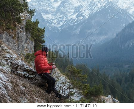 Well built mountain guide having rest at astonishing winter rocky landscape background