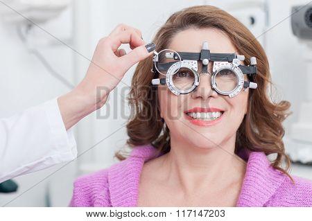 Cheerful female optician is examining human eyes