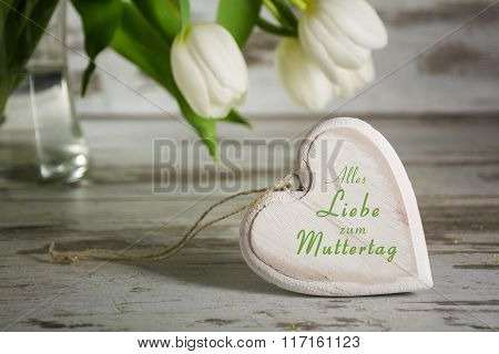 Wooden Heart Shape In Front Of White Tulips On A Gray Rustic Table For German Mothers Day
