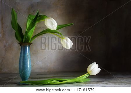 White Tulips And A Blue Porcelain Vase On An Old Wooden Table Against A Rustic Wall