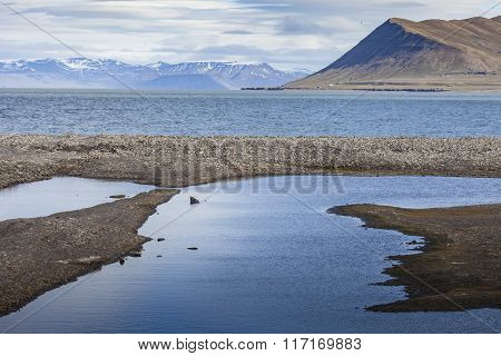 Beautiful Scenic View Of Blue Gulf Under Barren Mountain Range With Melting Snow Against The Backgro