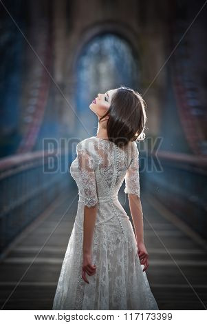 Lovely young lady wearing elegant white dress enjoying the beams of celestial light and snowflakes