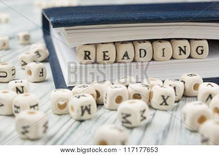 READING word written on wood block. Wooden ABC.