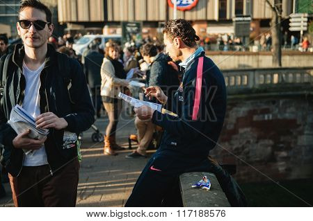 STRASBOURG FRANCE - FEB 6 2016: Man reading manifest while protesters claim rights during a demonstration against government's plan to extent the 'state of emergency' and for opened borders - poster