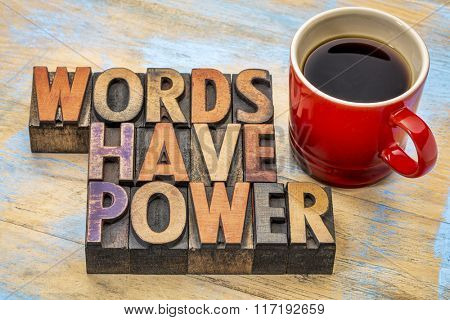 words have power  phrase in vintage letterpress wood type printing blocks stained by color inks with a cup of coffee