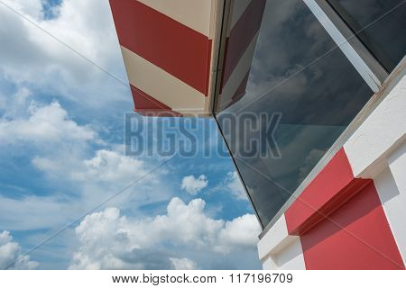 Air traffic control tower with red and white paint and scatterd cloud