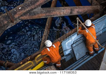 Wokers at jack up oil rig leg when checking everything in rig move operation