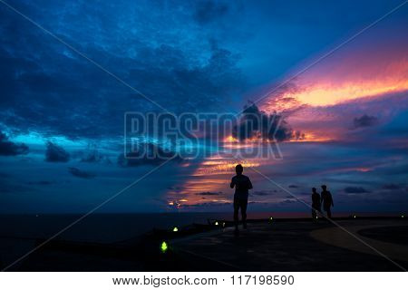 Silhouette of three men on the jack up oil and gas rig helipad when edge light on with dramatic sun ray in the sky