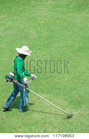 Gardener mowing grass with personnel protective equipment