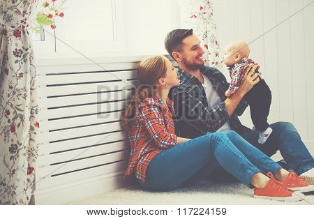 Happy Family Mother And Father Playing With A Baby