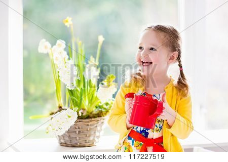 Little Girl Watering Spring Flowers