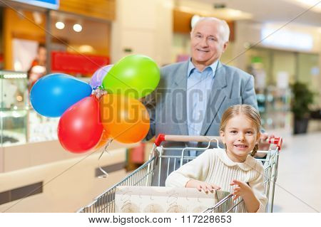 Grandfather with grandchild taking a look around mall.