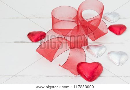 Red And Silver Foil Covered Heart Valentine Chocolates On White Rustic Wood Backround With Focus On