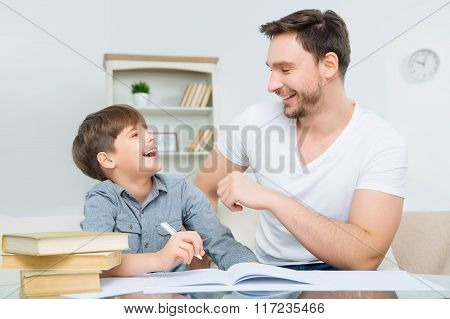 Pleased young father checking homework of son.