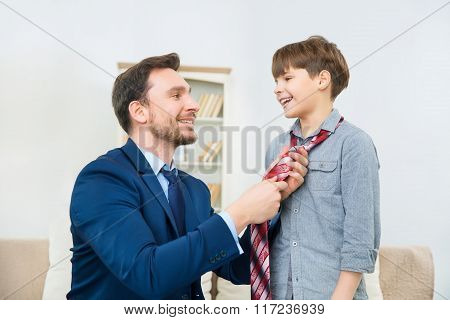 Young businessman helping smiling son to knot tie