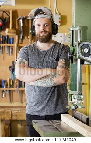 Smiling craftsman with safety mask and earmuffs in workshop
