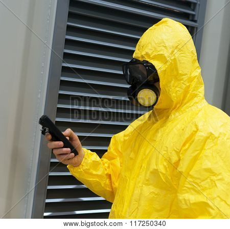 Worker in protective chemical suit checking radiation with geiger counter. poster