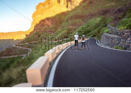Carefree couple running on the mountain roadside