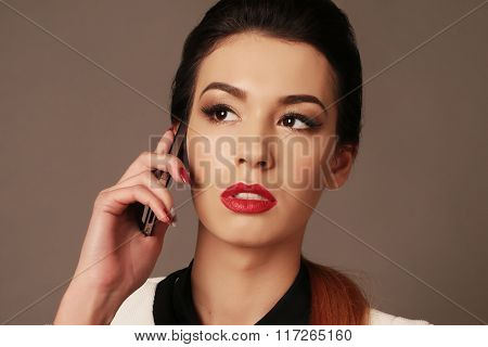 beautiful businesslike woman with dark hair and bright makeup, wears elegant suit