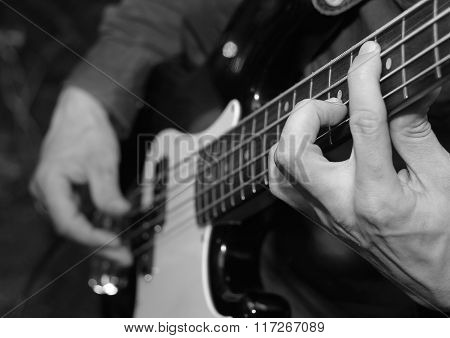 Musician plays bass guitar. Strings and fingers.