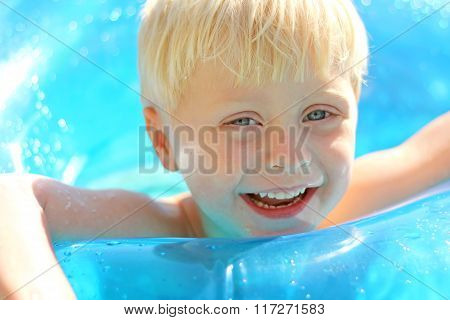 Adorable Laughing Blonde Kid Playing In Swimming Pool